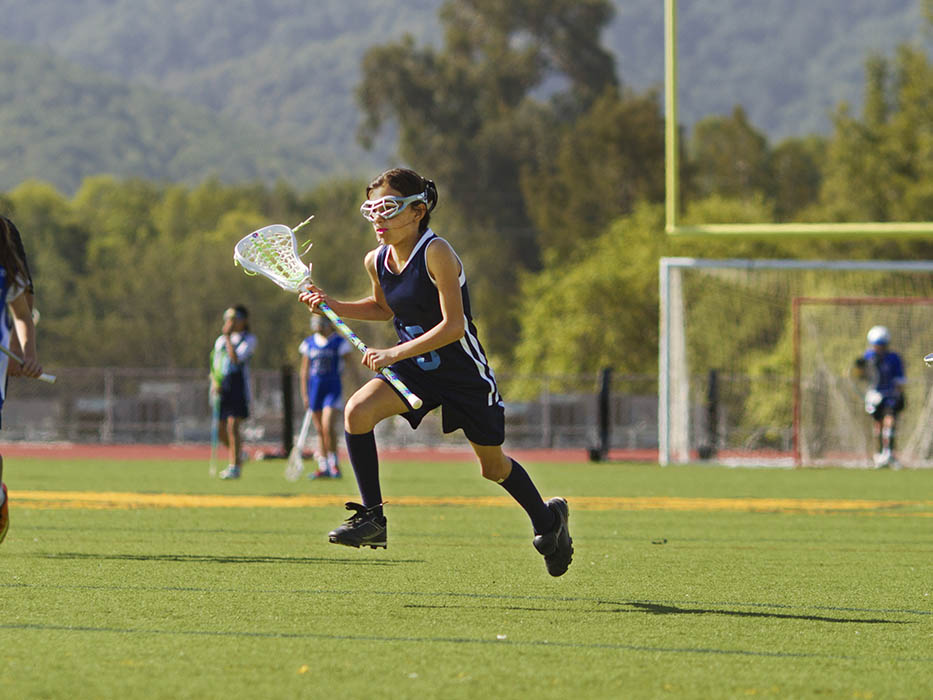 Girl Playing Lacrosse Mid Air
